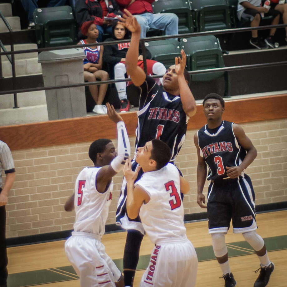 A. Jacobs of Port Arthur shoots the ball over Cabrera(no. 3) and Stevens(no. 5) Tuesday night at the East Chambers gymnasium in Winnie, Tx. Photo provided by Michael Reed Photo: Michael Reed / Michael Reed