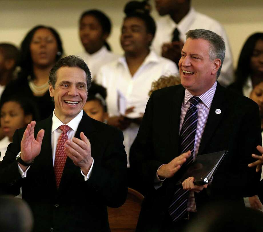 New York Gov. Andrew Cuomo, left, and New York City Mayor Bill de Blasio clap along with the choir during a Black, Puerto Rican, Hispanic and Asian Legislative Caucus Weekend church service at the Wilborn Temple on Sunday, Feb. 16, 2014, in Albany, N.Y. (AP Photo/Mike Groll) Photo: Mike Groll / AP