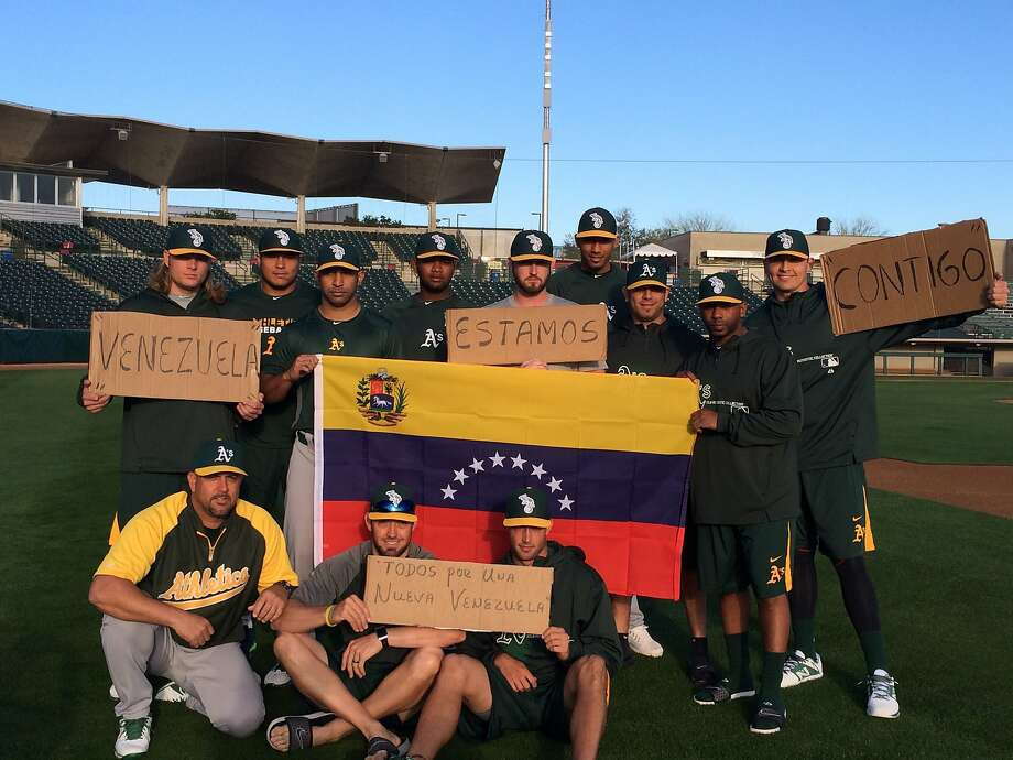 A's players, including the three Venezuelans at camp, hold up signs in solidarity with protesters in the strife-torn nation. Photo: Susan Slusser, The Chronicle