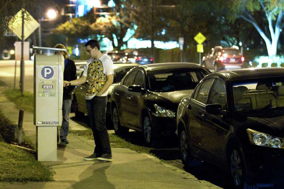Scott Black pays to park at a meter on Washington last Friday. Officials say parking revenue is below expectations, potentially delaying improvements like wider sidewalks and trees. Photo: Brett Coomer, Staff / © 2014 Houston Chronicle