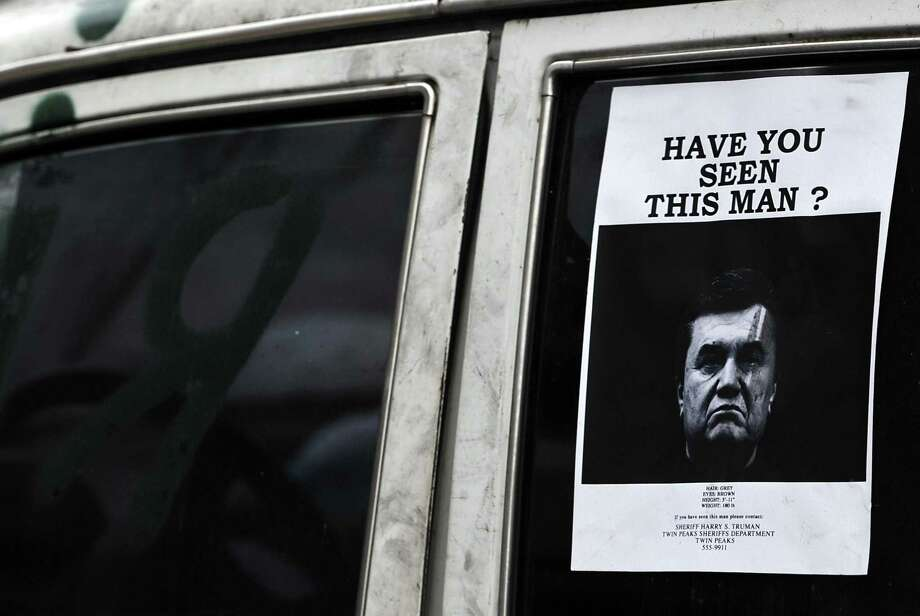 A poster with ousted Ukrainian President Viktor Yanukovych's photo is on a car window in Kiev, the capital. Ukraine issued an arrested warrant for Yanukovych on Monday. Photo: Louisa Gouliamaki / Getty Images / AFP