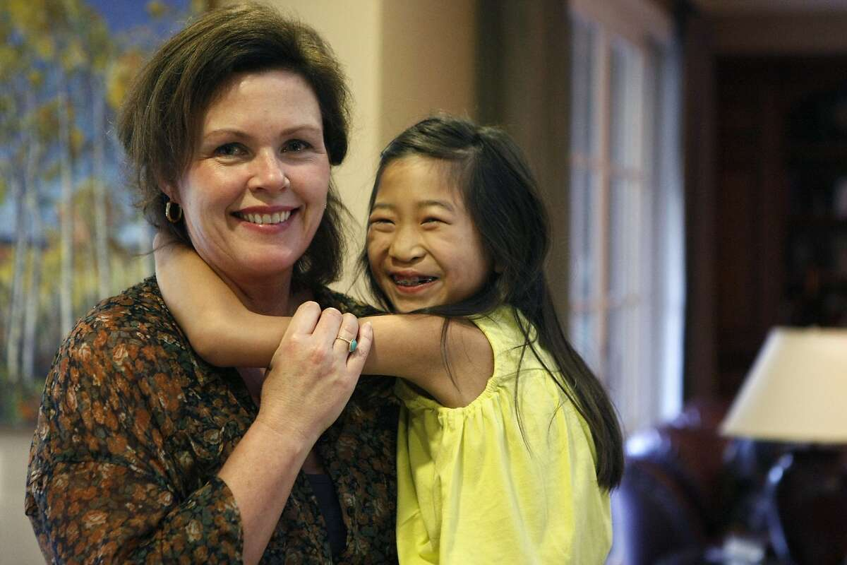 Kathleen O'Rourke, 48, (left) holds her daughter, Liping Sheridan, 8, in their home on February 21, 2014 in Los Altos, Calif. O'Rourke's son Louis Sheridan, 15, was diagnosed with Lyme disease when he was 9 years old, and his diagnosis helped O'Rourke have her own Lyme disease diagnosed 4 years after she contracted it.