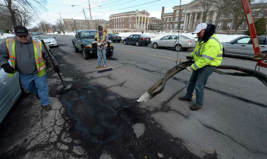 Jeff Hunt, right, of the Albany Department of General Services sprays a mixture of stone and liquid blacktop in to a pothole Monday morning, Feb. 24, 2014, on Western Avenue in Albany, N.Y. (Skip Dickstein/Times Union) Photo: Skip Dickstein / 00025865A