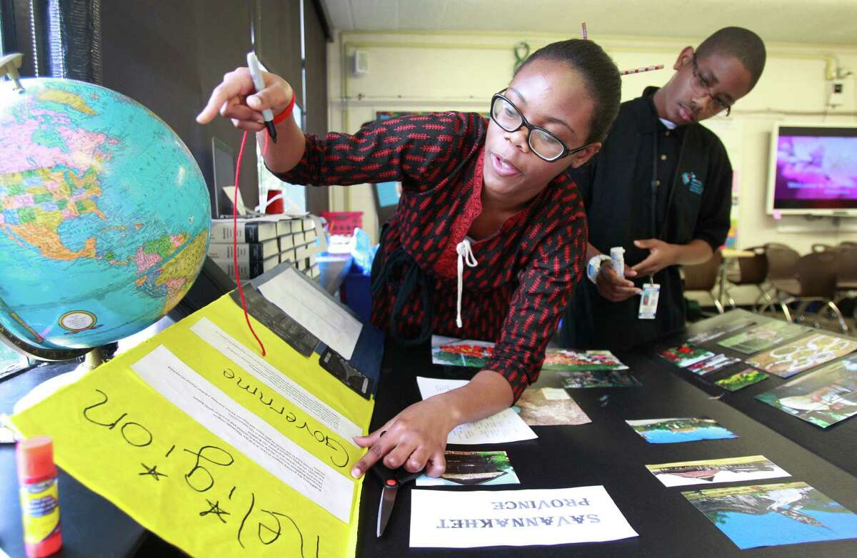 Chisom Anyanwu, 15, left, and Blake Gomez, 14, work on a project about Laos at the HISD's Energy Institute High School. The school is getting a new home, and could have some green design elements thought up by UH students.