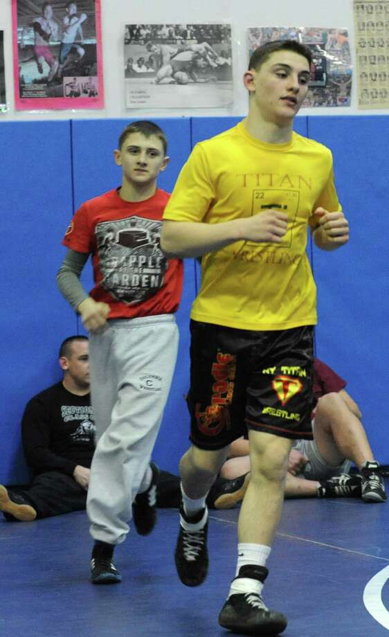 Wrestlers Jim Devine, right, and his brother John jog while warming up for practice at Columbia High School on Monday, Feb. 24, 2014 in East Greenbush, N.Y.  (Lori Van Buren / Times Union) Photo: Lori Van Buren / 00025859A