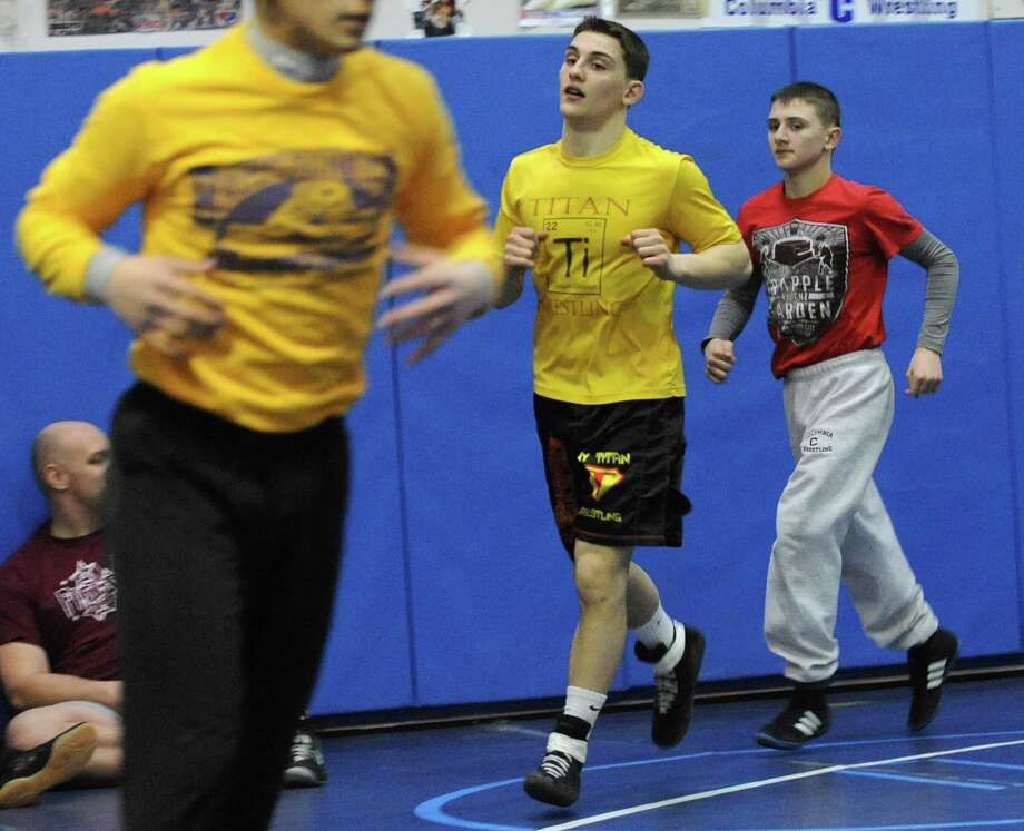 Wrestlers Jim Devine, center, and his brother John, right, jog while warming up for practice at Columbia High School on Monday, Feb. 24, 2014 in East Greenbush, N.Y.  (Lori Van Buren / Times Union) Photo: Lori Van Buren / 00025859A