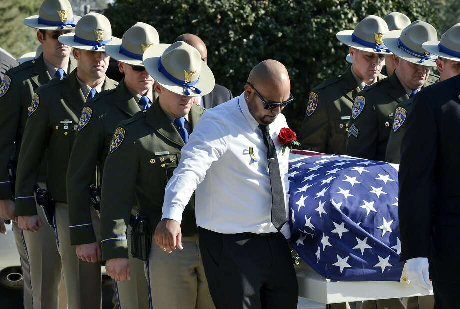 The casket for California Highway Patrol Officer Juan Gonzalez is carried to the North Tulare Public Cemetery. Gonzalez and Officer Brian Law died Feb. 17 in a crash on Route 99 while responding to a traffic accident. Photo: Eric Paul Zamora, Associated Press