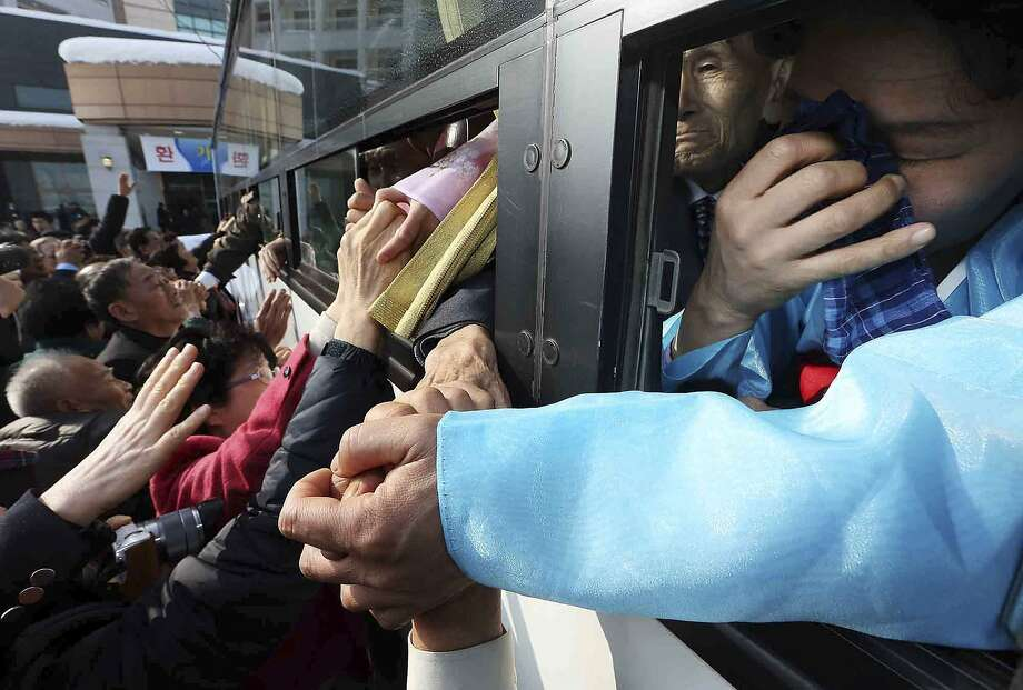 South Koreans hold hands with their North Korean family members (in bus) as they bid farewell after their three-day temporary family reunion at the Mount Kumgang resort in North Korea, February 25, 2014.The six days of family reunions take place under the cloud of a U.N. report on human rights abuses in North Korea, which investigators have said were comparable to Nazi-era atrocities. A group of South Koreans crossed the world's most heavily fortified border on Sunday, a frontier that separates two countries that remain at war after their conflict ended in an armistice rather than a peace treaty.  REUTERS/Lee Ji-eun/Yonhap (NORTH KOREA - Tags: SOCIETY TPX IMAGES OF THE DAY) ATTENTION EDITORS - NO SALES. NO ARCHIVES. FOR EDITORIAL USE ONLY. NOT FOR SALE FOR MARKETING OR ADVERTISING CAMPAIGNS. THIS IMAGE HAS BEEN SUPPLIED BY A THIRD PARTY. IT IS DISTRIBUTED, EXACTLY AS RECEIVED BY REUTERS, AS A SERVICE TO CLIENTS. SOUTH KOREA OUT. NO COMMERCIAL OR EDITORIAL SALES IN SOUTH KOREA Photo: Yonhap, Reuters