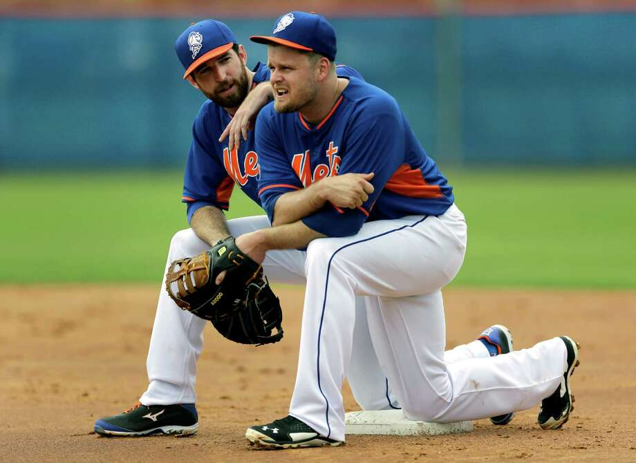 New York Mets' Ike Davis, left, and Lucas Duda kneel on first base while watching teammates participate in a fielding drill during spring training baseball practice Saturday, Feb. 22, 2014, in Port St. Lucie, Fla. (AP Photo/Jeff Roberson) ORG XMIT: FLVR113 Photo: Jeff Roberson / AP