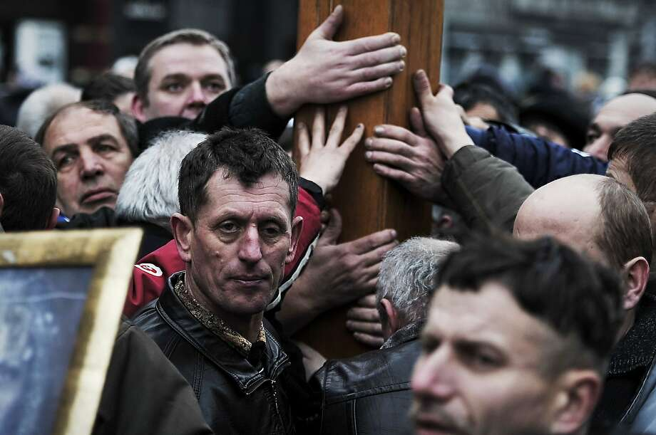 """People hold a large cross during a religious procession for the victims of recent clashes between protesters and police in Kiev on February 24, 2014. Ukraine issued an arrest warrant for ousted president Viktor Yanukovych on February 24 as the country's new rulers launched a probe over the """"mass murder"""" of protesters in a week of carnage in Kiev. Ukraine said it will need $35 billion in urgent foreign assistance and asked Western donors to convene an international conference within two weeks that could agree a financial rescue plan. TOPSHOTS/AFP PHOTO/ LOUISA GOULIAMAKILOUISA GOULIAMAKI/AFP/Getty Images Photo: Louisa Gouliamaki, AFP/Getty Images"""