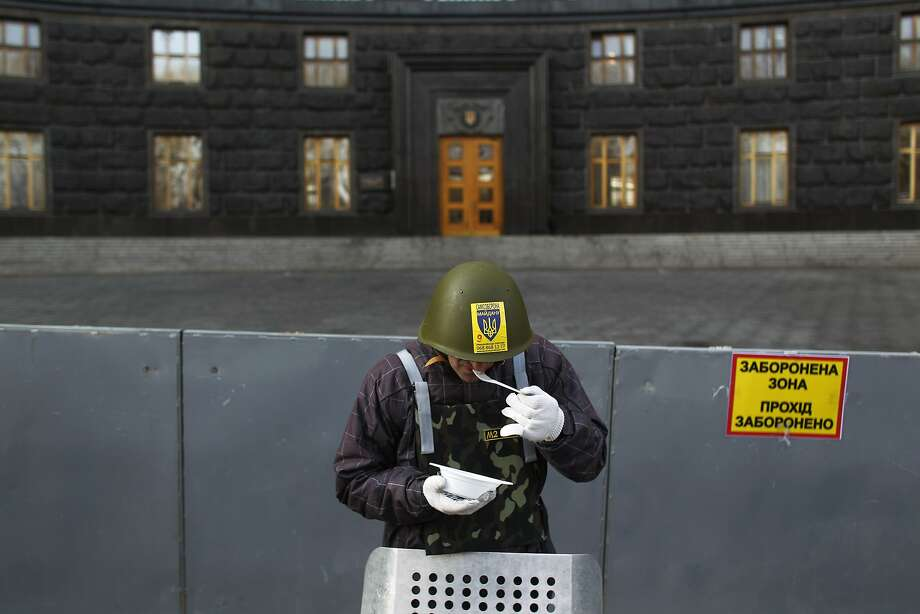 A protester eats as he stands guard in front of the Ukrainian government building in Kiev, Ukraine, Monday, Feb. 24, 2014. Ukraine's acting government issued a warrant Monday for the arrest of President Viktor Yanukovych, last reportedly seen in the pro-Russian Black Sea peninsula of Crimea, accusing him of mass crimes against protesters who stood up for months against his rule. (AP Photo/Marko Drobnjakovic) Photo: Marko Drobnjakovic, Associated Press
