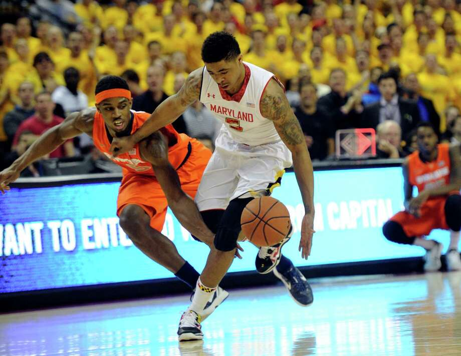 Syracuse forward C.J. Fair, left, fights for the ball against Maryland guard Nick Faust (5) during the second half of an NCAA college basketball game, Monday, Feb. 24, 2014, in College Park, Md. Fair was called for a foul on the play. Syracuse won 57-55. (AP Photo/Nick Wass) ORG XMIT: CPX112 Photo: Nick Wass / FR67404 AP