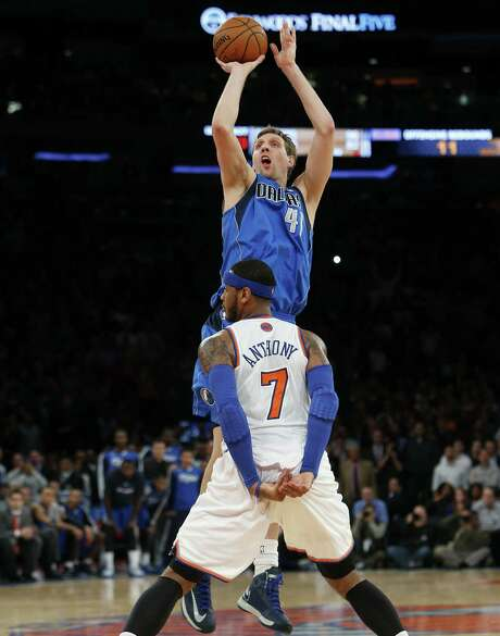 """The Mavericks' Dirk Nowitzki shoots the 19-foot game-winner over Carmelo Anthony to give Dallas a 110-108 victory, its third in a row. The basket offset Anthony's game-high 44 points. """"It was like a needle in a balloon right there,"""" Anthony said. """"It sucks all the air out of you."""" Photo: Jason DeCrow / Associated Press / FR103966 AP"""