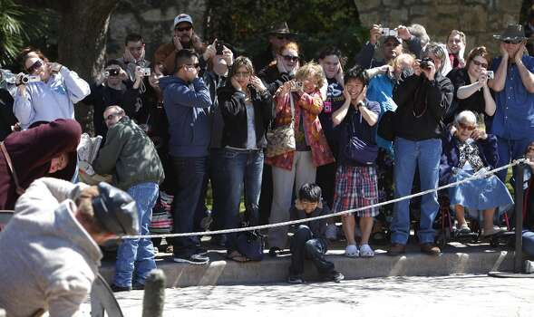 People covered their ears before the firing of a cannon in Alamo Plaza during a re-enactment of the battle at the Alamo on Saturday, March 5, 2011. Photo: Kin Man Hui, Express-News