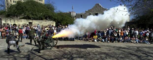 Actors of the San Antonio Living History Association fire off a cannon that marked the beginning of the Alamo siege of 1836. Photo: Kin Man Hui, Express-News