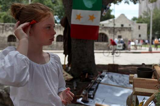 Elise Brown, 9, of Wimberley, tucks a flower behind her ear as she portrays an Anglo settler with members of the San Antonio Living History Society on Aug. 18, 2012. Photo: Lisa Krantz, Express-News