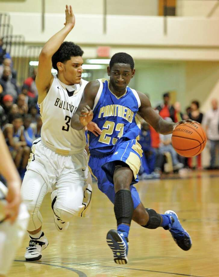 Ozen's Jordan Hunter (23) dribbles past Nederland's Diondre Frank (3) during third period action Tuesday in Nederland.