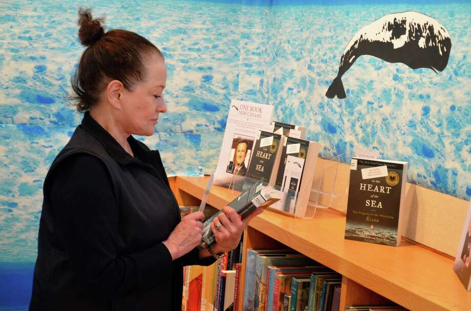 "New Canaan Library patron Myrna Lee looks at a copy of ""In the Heart of the Sea,"" the book the library chose to launch its first One Book New Canaan project this winter. The author, Nathaniel Philbrick, will visit New Canaan to talk about his book on April 4. Photo: Nelson Oliveira / New Canaan News"