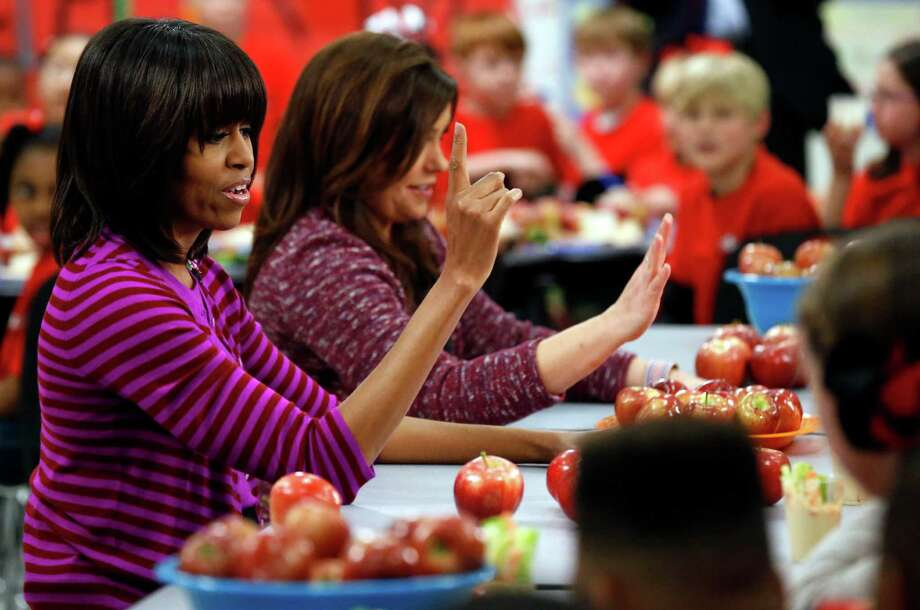 This Feb. 27, 2013 file photo shows first lady Michelle Obama and Food Network chef Rachel Ray discussing lunches with students from the Eastside and Northside Elementary Schools in Clinton, Miss. Moving beyond the lunch line, new rules expected to be proposed by the White House and the Agriculture Department Tuesday, Feb. 25, 2014, would limit marketing of unhealthy foods in schools, phasing out the advertising of sugary drinks and junk foods around school campuses and ensuring that other promotions in schools are in line with health standards that apply to school foods.Click through the slideshow to see more images of school lunches through the years. Photo: Rogelio V. Solis, AP / AP