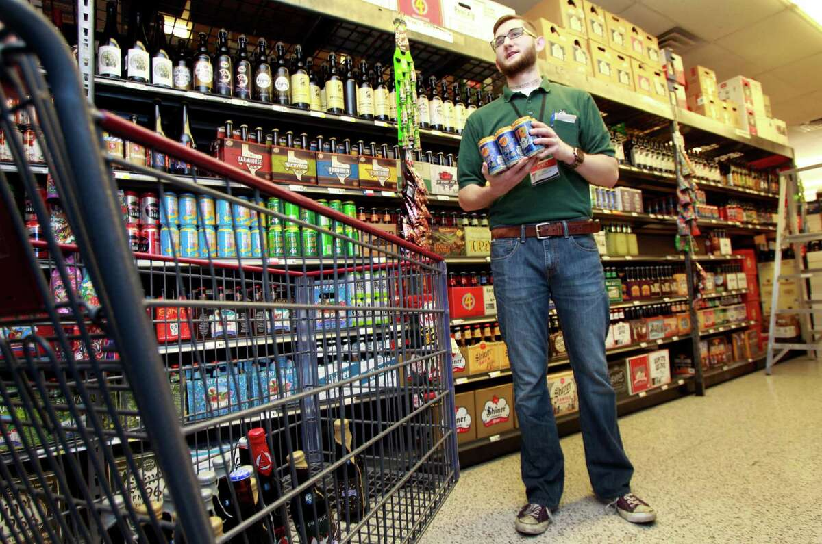 Joey Williams, beer department manager at Spec's, 2410 Smith, talks to customers in the Texas beer section Friday, Feb. 21, 2014, in Houston. ( Melissa Phillip / Houston Chronicle )