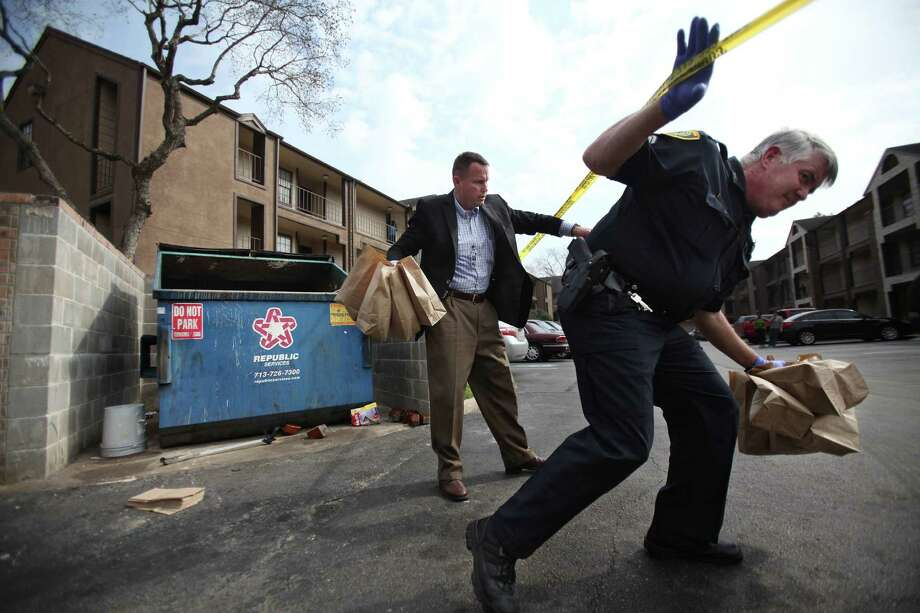 HPD Investigators walk away with evidence from the white trash bag where a newborn baby boy was found on Feb. 25, 2014, in Houston.  According to Carlos Michel, maintenance worker at The Reserve at Windmill Lakes Apartment complex, he heard a sound coming from the dumpster which he thought is was a cat at first. When he heard sound again, after throwing a bucket of trash in the dumpster, he reached in and pulled a white trash bag with a newborn baby inside. Photo: Mayra Beltran, Houston Chronicle / © 2014 Houston Chronicle