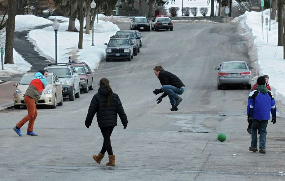 Taylor Wright-Sanson, teacher and graduate of The Waldorf School of Saratoga Springs, third from left, jumps to avoid being hit by a ball thrown by his student Alex Mercier of Ballston Spa during a game of Poison Ball in Congress Park on Tuesday, Feb. 25, 2014 in Saratoga Springs, N.Y. The teacher brought his students to the park to play as part of the school's elective week.  (Lori Van Buren / Times Union) Photo: Lori Van Buren / 00025881A