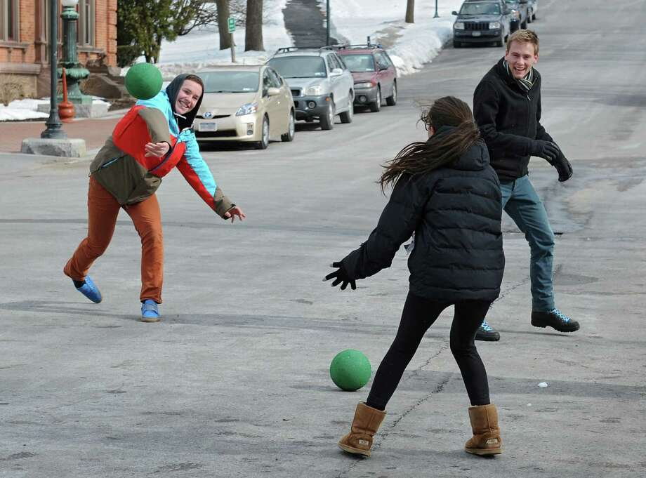 Taylor Wright-Sanson, teacher and graduate of The Waldorf School of Saratoga Springs, right, watches as his student Alex Mercier of Ballston Spa throws a ball at Flavie Doyon of Saratoga Springs during a game of Poison Ball in Congress Park on Tuesday, Feb. 25, 2014 in Saratoga Springs, N.Y. The teacher brought his students to the park to play as part of the school's elective week.  (Lori Van Buren / Times Union) Photo: Lori Van Buren / 00025881A