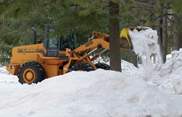 A tractor moves large snow banks from a parking lot  in Saratoga Spa State Park on Tuesday, Feb. 25, 2014 in Saratoga Springs, N.Y.  (Lori Van Buren / Times Union) Photo: Lori Van Buren / 00025881A