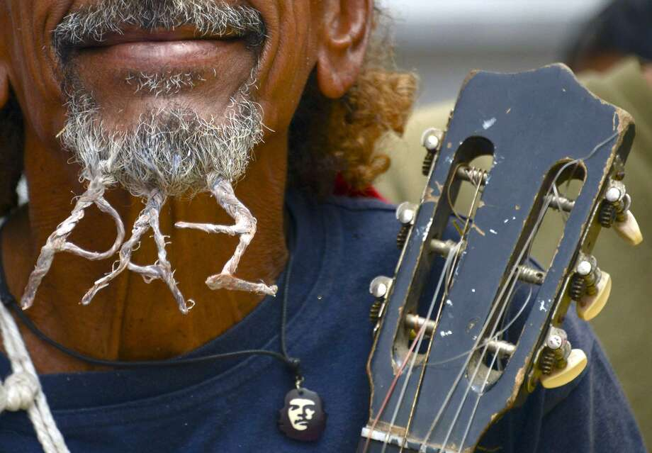 "Give peace a chin:A pro-government supporter whose braided whiskers spell ""peace"" takes part in the ""March of Seniors"" in Caracas. Hundreds of demonstrators, mostly elderly, marched in support of President Nicolas Maduro. An opposition rally a day earlier turned violent, leaving 10 people dead. Photo: Raul Arboleda, AFP/Getty Images"