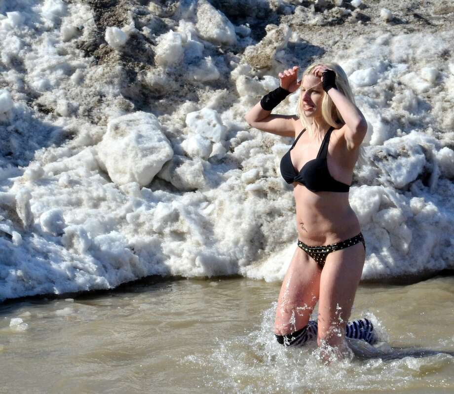 C'mon in, the water's f-f-f-fine! In Geneva State Park, Ohio, Jennifer Stitts joins the many brave souls worldwide who think polar-bear plunging in the middle of winter is a good idea. Photo: Warren Dillaway, Associated Press