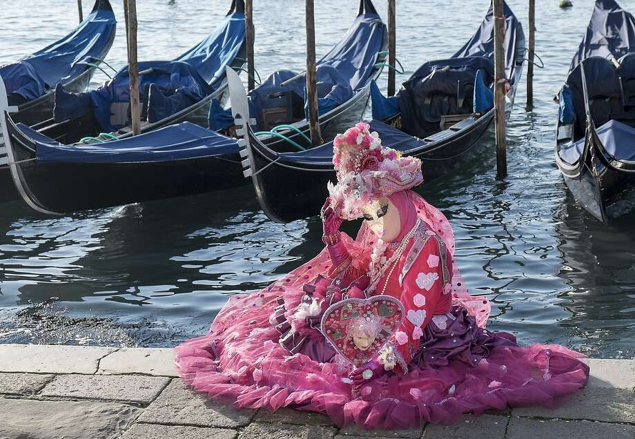 The belle of the canal: A signorina  dressed in a carnival costume poses in front of gondolas in St. Mark's Square. The Carnival of Venice runs from Feb. 15 to March 4. Photo: Marco Secchi, Getty Images