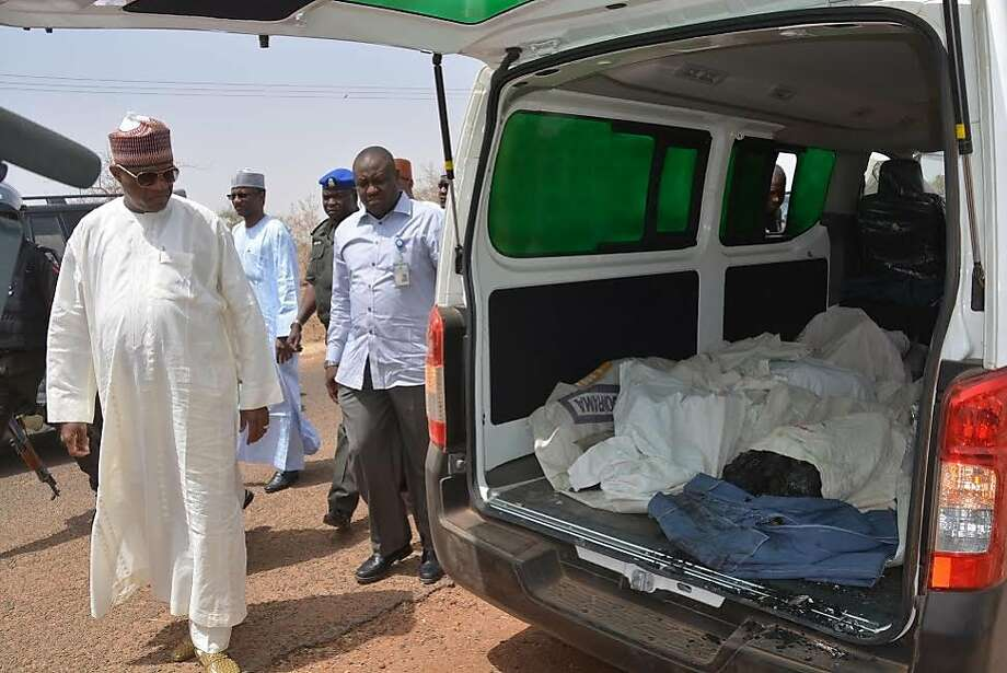 Ibrahim Gaidam (left), governor of Yobe state, looks at bodies of students killed by Islamic militants in the city of Damaturu. The militants believe getting a Western education goes against Islam. Photo: Associated Press
