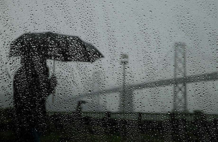 A pedestrian carries an umbrella while walking near the Bay Bridge on February 6th in San Francisco. The San Francisco Bay Area will getting much needed rain tomorrow with system expected to bring up to two inches of rain to the region. Photo: Justin Sullivan / Justin Sullivan / Getty Images / 2014 Getty Images