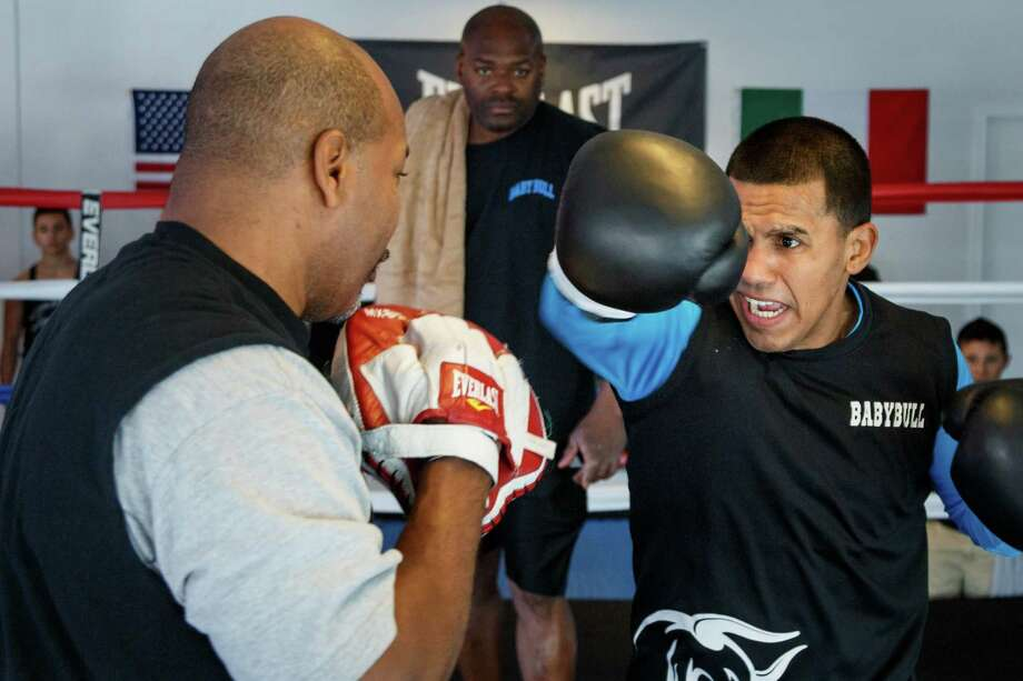 Four-time world boxing champion Juan Diaz, right, of Houston warms up in the ring with trainer Derwin Richards, left, during the grand opening of the Baby Bull Boxing Academy, Saturday, Jan. 18, 2014, in Houston.  ( Michael Paulsen / Houston Chronicle ) Photo: Michael Paulsen, Staff / © 2014 Houston Chronicle