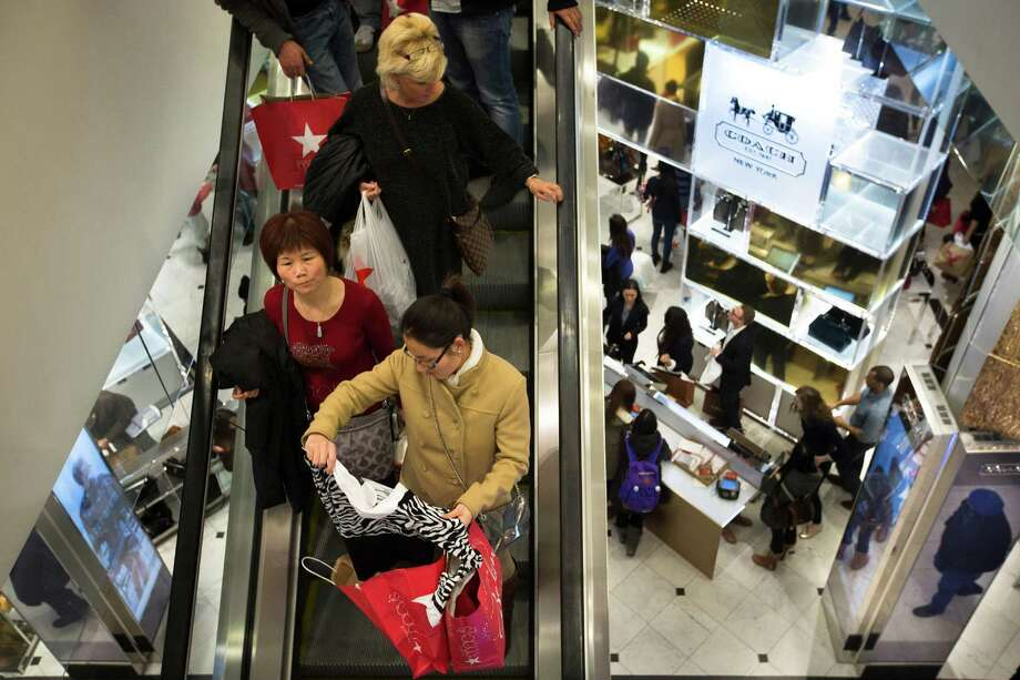 In this Nov. 28, 2013, file photo, shoppers descend on an escalator at the Macy's Herald Square store in New York. Consumer confidence fell more than forecast in February amid about the U.S. economy's direction, restraining spending, according to a report on Tuesday from the Conference Board. Photo: John Minchillo, Associated Press / Associated Press contributed