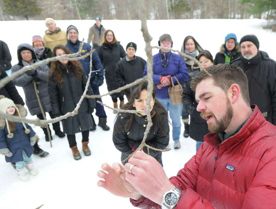 At right, Steve Conaway, stewardship & outreach manager for the Greenwich Land Trust, speaks about the Aspen tree, a branch of which he is holding, while leading a winter nature walk at Duck Pond Hill, Greenwich, Conn., Tuesday, Feb. 25, 2014. Conaway spoke about how wildlife survives the winter and how to identify trees and plants without their leaves. Photo: Bob Luckey / Greenwich Time