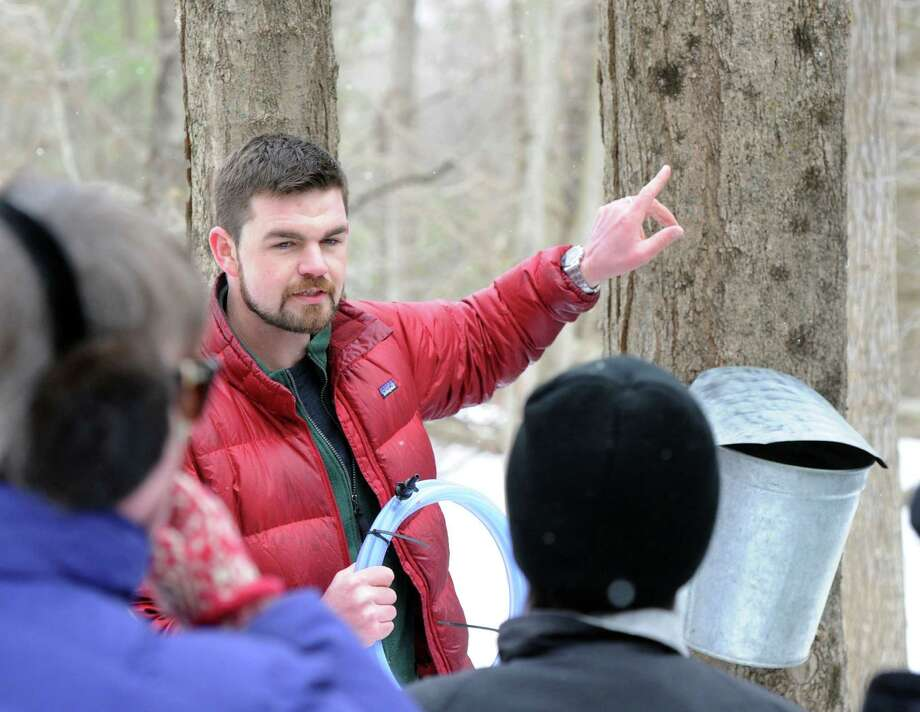 Steve Conaway explains the sap collecting process for maple syrup during the Greenwich Land Trust winter nature walk at Duck Pond Hill, Greenwich, Conn., Tuesday, Feb. 25, 2014. Conaway, a stewardship & outreach manager for the trust, led the tour and spoke about how wildlife survives the winter and how to identify trees and plants without their leaves. Photo: Bob Luckey / Greenwich Time