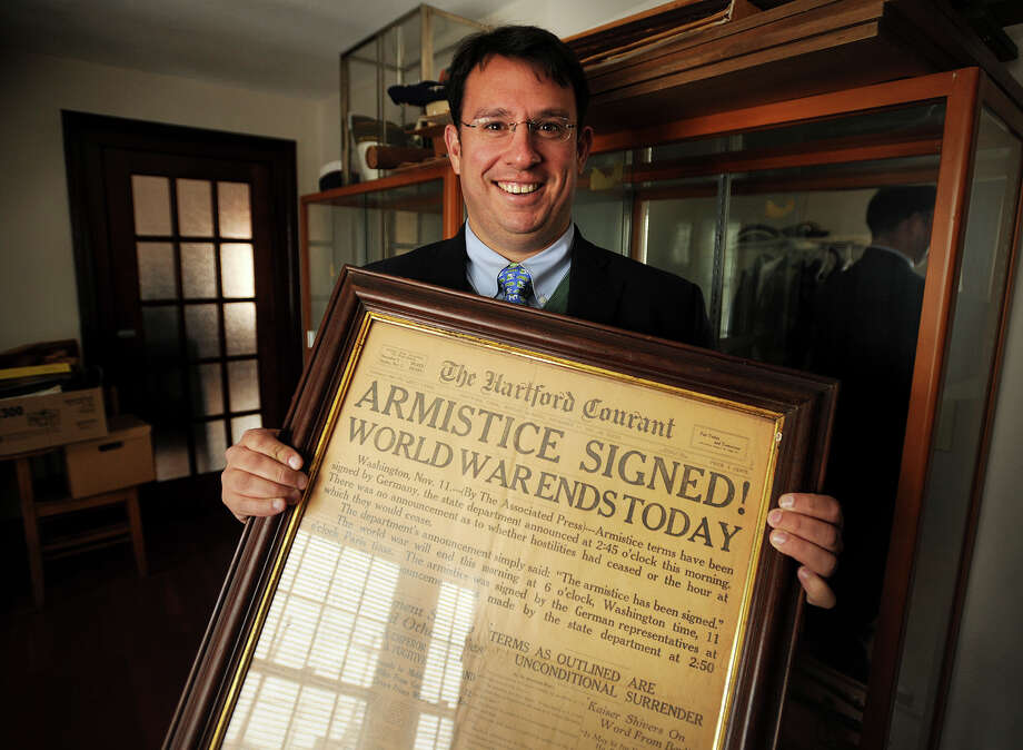 Milford Mayor Ben Blake holds a framed newspaper announcing the end of World War One, part of a large collection of military artifacts at the Fowler Memorial Building in Milford, Conn. on Tuesday, February 25, 2014. Photo: Brian A. Pounds / Connecticut Post