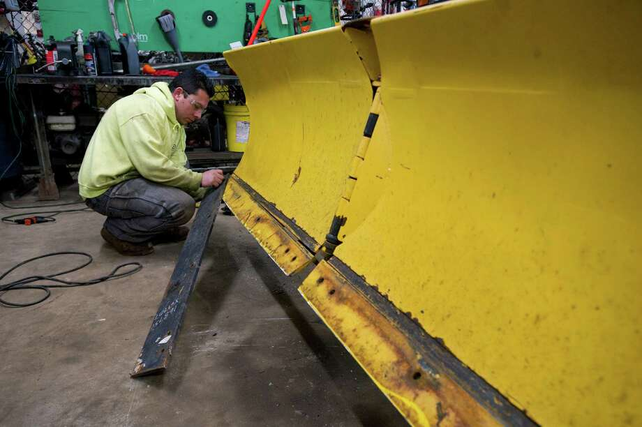 Wilbur Arana replaces a plow blade at Eastern Land Management in Stamford, Conn., on Tuesday, February 25, 2014. Photo: Lindsay Perry / Stamford Advocate