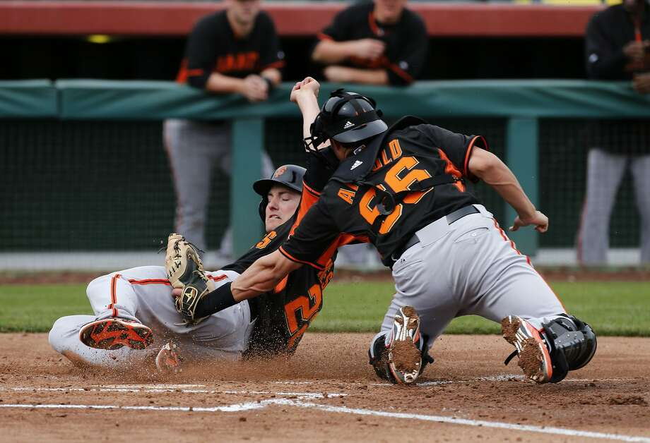 Above, Giants outfielder Roger Kieschnick is tagged by catcher Jeff Arnold to end an intrasquad game at Scottsdale Stadium. Below, the collision between Marlins outfielder Scott Cousins and Giants catcher Buster Posey that ended Posey's 2011 season. Photo: Michael Macor, The Chronicle