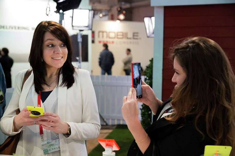 A woman takes a picture with a Nokia Lumia 1520 phone as her friend smiles at the Mobile World Congress in Barcelona, Spain, Tuesday, Feb. 25, 2014. (AP Photo/ Marce Martinez) ORG XMIT: MS101 Photo: Marce Martinez / AP