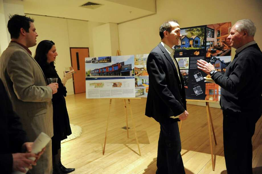 Rob Brass, center, whose home won the honor award for residential small project, talks with architect Dave Dembling, right, during the 2013 Design Awards Reception and Awards Ceremony on Thursday, Feb. 20, 2014, at the Arts Center of the Capital Region in Troy, N.Y. Scott Townsend of 3tarchitects, not pictured, designed the house, shown at right. The honor award winner for renovation, addition and adaptive use is Malone Middle School, shown at left. (Cindy Schultz / Times Union) Photo: Cindy Schultz / 00025843A