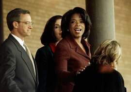 Talk show host Oprah Winfrey, right, slips out the back door of the federal courthouse in Amarillo, Texas, Wednesday evening, Jan. 21, 1998 after the second day of her beef defamation trial. Testimony in the trial is expected to begin Thursday. (AP Photo/Eric Gay)