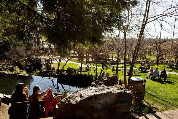 Customers enjoy wine in an outdoor garden area at Boeger's Winery in Placerville, Calif., Saturday, February 21, 2014.