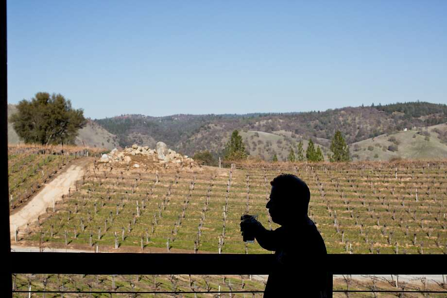 Volunteer Gary Ritz tastes beer on the patio that hangs above the vineyards with a view of the Sierra foothills at Gold Hill Vineyard and Brewery in Placerville. Photo: Jason Henry, Special To The Chronicle