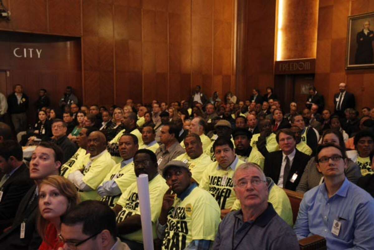 Houston Yellow Cab drivers attend Houston mayor's meeting at City Hall, Tuesday, Feb. 25, 2014, wearing yellow T-shirts to protest the Uber company. Uber allows anyone to request a ride via mobile app, text message or the web.