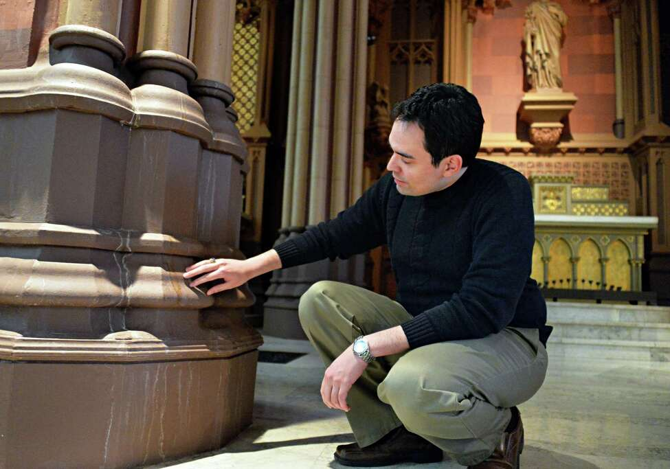 Brian Gurley, music director & organist at the Cathedral of the Immaculate Conception, shows where water had leaked down pillars on both transepts on either side of the altar Tuesday, Feb. 25, 2014, in Albany, N.Y. (John Carl D'Annibale / Times Union)