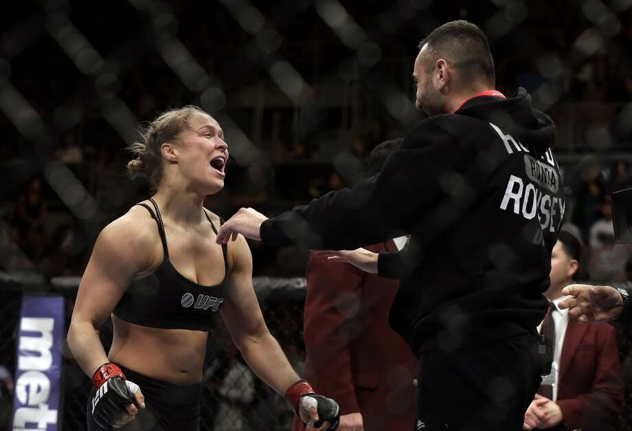 Ronda Rousey, left, hugs her trainer Edmond Tarverdyan after defeating Sara McMann in a UFC 170 mixed martial arts women's bantamweight title fight on Saturday, Feb. 22, 2014, in Las Vegas. (AP Photo/Isaac Brekken) Photo: Isaac Brekken, Associated Press
