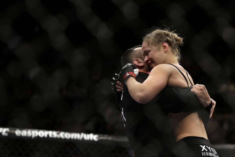 Ronda Rousey, right, hugs her trainer Edmond Tarverdyan after defeating Sara McMann in a UFC 170 mixed martial arts women's bantamweight title fight on Saturday, Feb. 22, 2014, in Las Vegas. (AP Photo/Isaac Brekken) Photo: Isaac Brekken, Associated Press