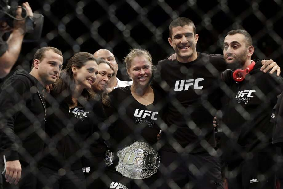 Ronda Rousey, center, poses with her team following a UFC 170 mixed martial arts women's bantamweight title fight against Sara Mcmann on Saturday, Feb. 22, 2014, in Las Vegas. (AP Photo/Isaac Brekken) Photo: Isaac Brekken, Associated Press